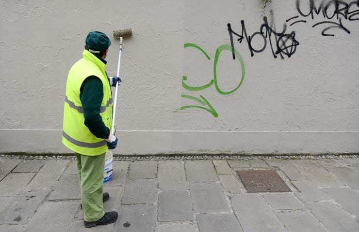 man cleaning graffiti off wall