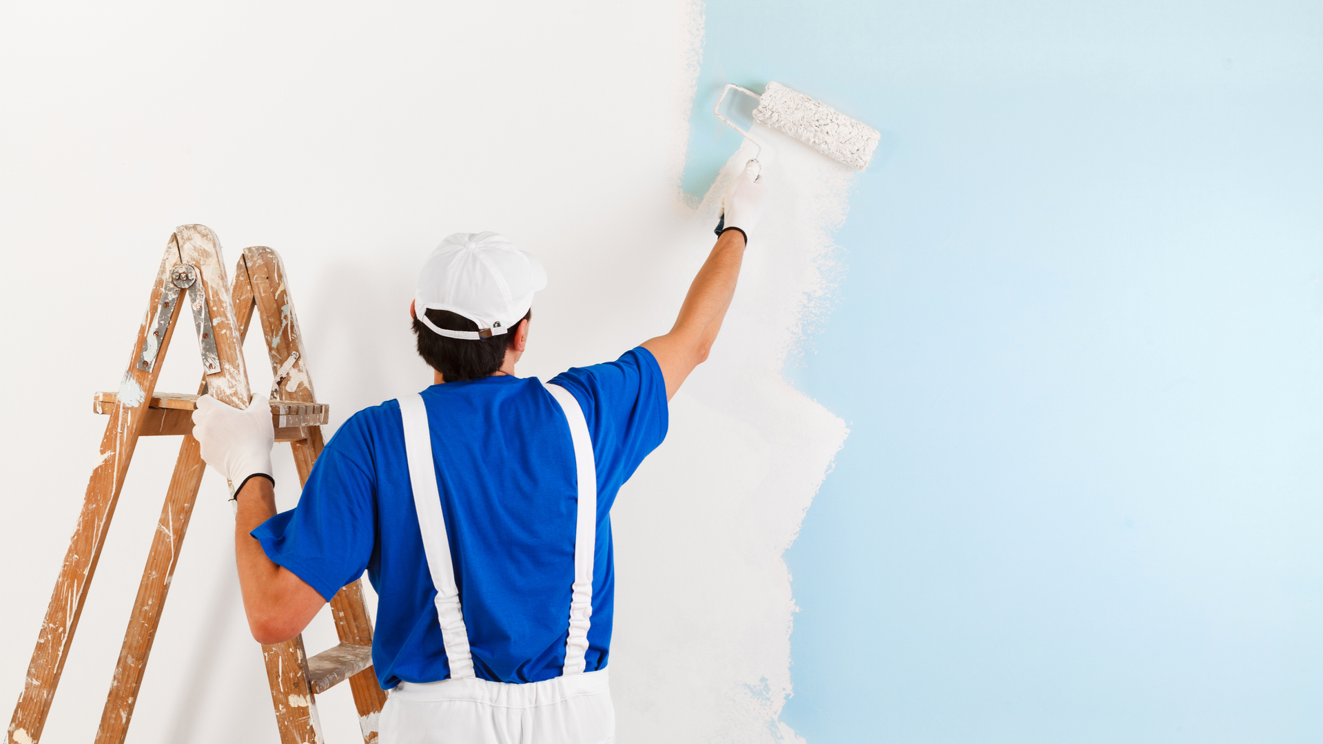 Professional painter painting home in winter