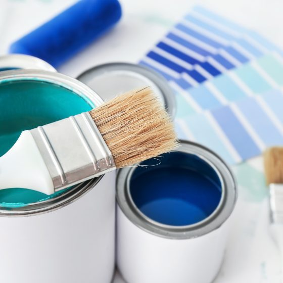 An amount of paint and paint supplies including paint cans and brushes